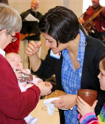 Emmy Kegler blessing a baby at communion at Light of the World in 2013.