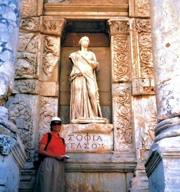 Reta Finger with a statue of Sophia (Lady Wisdom) in a niche in the facade of the ancient library of Ephesus.