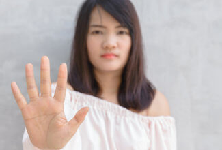 A woman holding up her hand as if to say stop