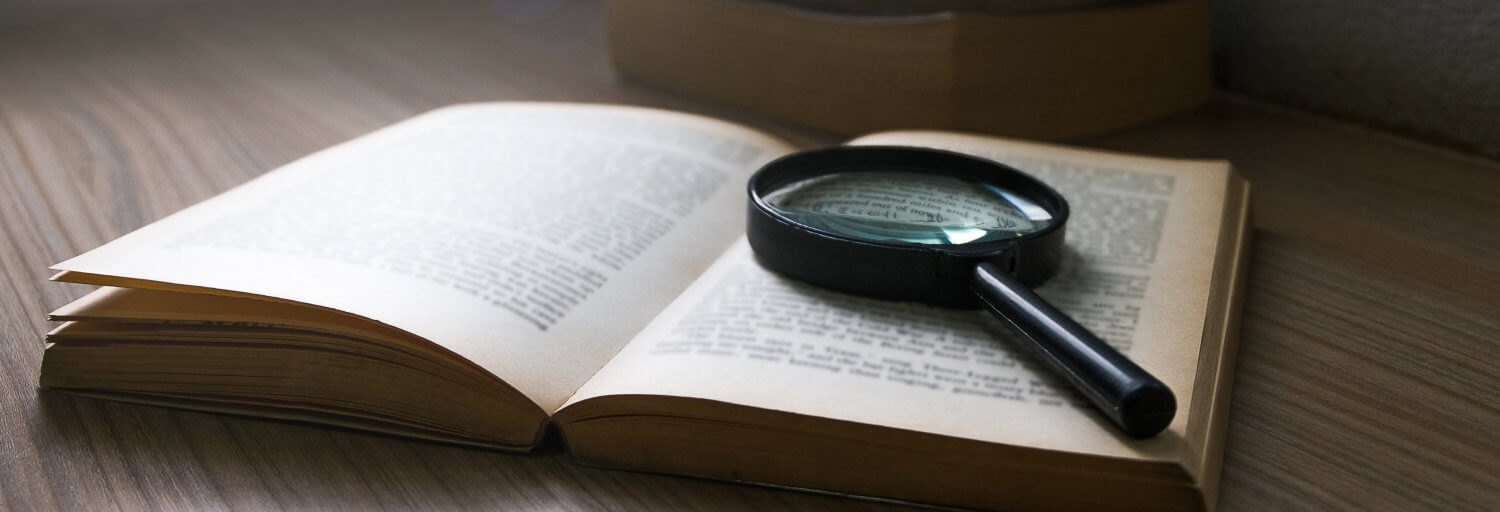 An open book and magnifying glass