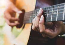 Woman's hands playing the guitar