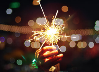 Sparkler in a hand with blurry lights in the background