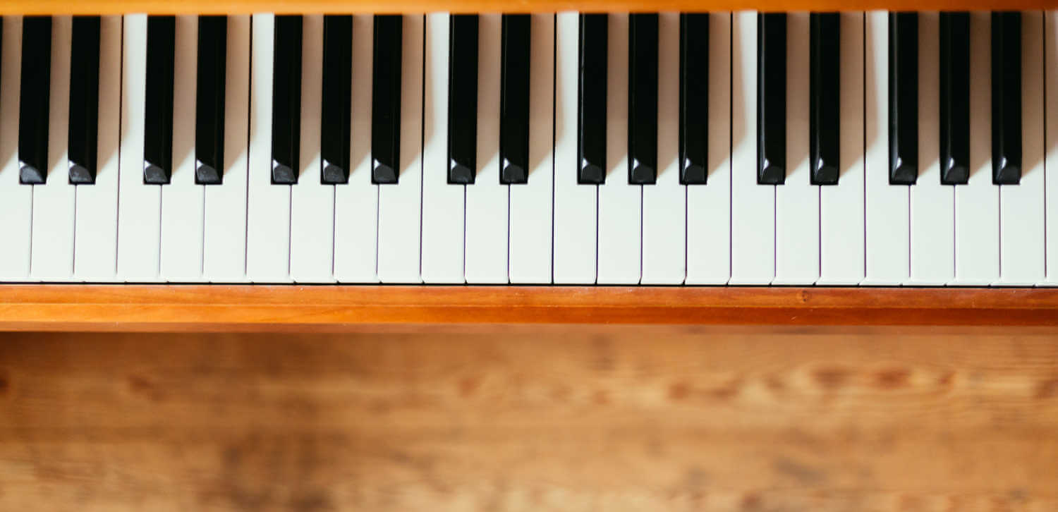 Piano keyboard over a wooden floor